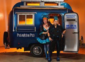 Annie Sprinkle and Beth Stephens standing in front of a van