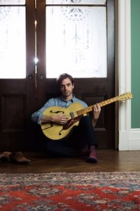 Photo of Val Emmich sitting in front of a door playing a guitar