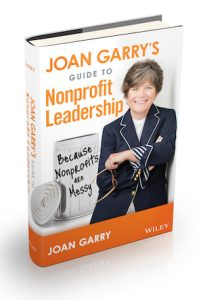 Photo of the book Joan Garry's Guide to Nonprofit Leadership; picture of Joan Garry standing and smiling