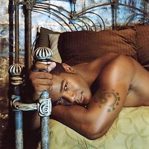 Tyler Knight laying on a bed grabbing a bedpost